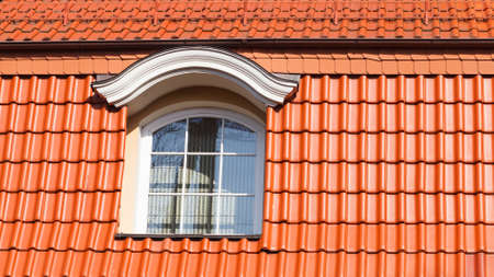 New, modern roof made of red ceramic tiles and a large attic window