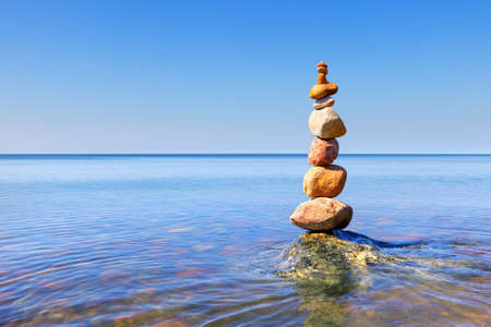 Rock zen pyramid of colorful pebbles standing in the water on the background of the sea. Concept of balance, harmony and meditation Фото со стока