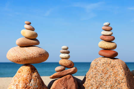 Rock zen pyramid of colorful pebbles on a beach on the background of the sea. Concept of balance, harmony and meditation