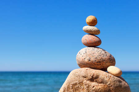 Rock zen pyramid of white and pink pebbles on the beach. Concept of Life balance, harmony and meditation Foto de archivo