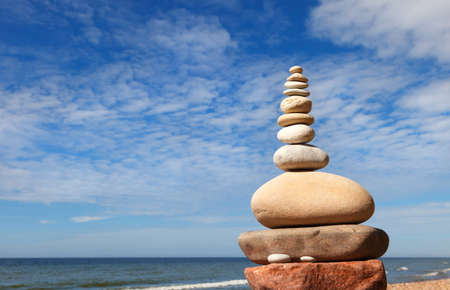 Rock zen pyramid of white and pink pebbles on the beach. Concept of Life balance, harmony and meditation