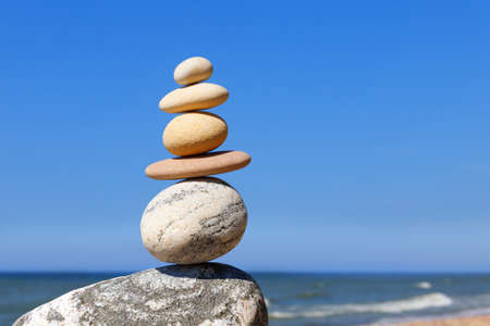Rock zen Pyramid of balanced stones against the background of the sea and blue sky. Concept of balance, harmony and meditation
