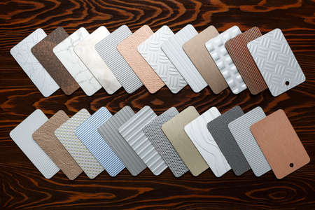 Metal laminate samples laid out on a brown wooden background. Flat lay, Top view