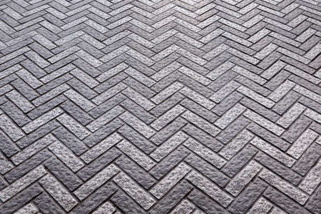 Grey paving slabs made of natural stone laid with a herringbone pattern. Top view