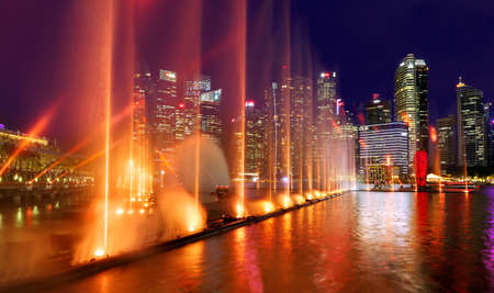 SINGAPORE-November 29, 2019: Night show of fountains in Singapore near the Marina Bay Sands hotel against the skyscrapers of the business center