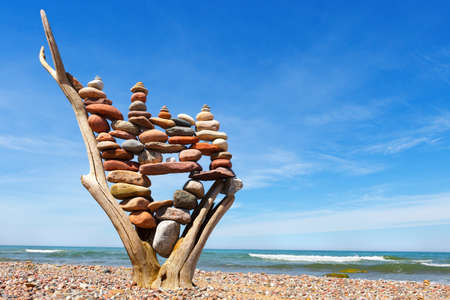 stack of multicolored balanced stones on an old wooden snags, on a blue sky and sea background. Concept of harmony and balance. copy space Standard-Bild