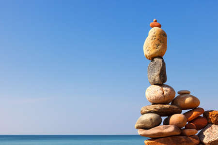 Rock zen pyramid of white and pink pebbles on the beach. Concept of Life balance, harmony and meditation. copy space