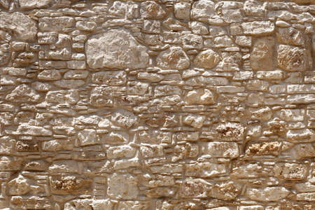 Ancient wall of light, yellow Sandstone of different shapes and sizes. Background image, texture