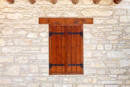 Closed, dark wooden shutters on a light sandstone wall Standard-Bild