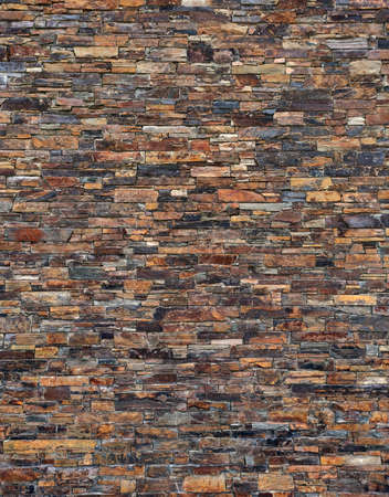 wall of dark brown, natural slate stone. background image, texture