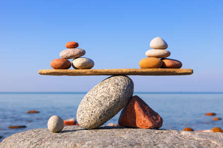 Rock zen pyramid of colorful pebbles on a sandy beach. Concept of balance, harmony and meditation