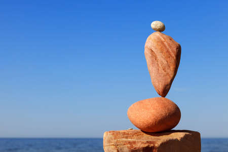 Rock zen pyramid of red pebbles on the beach. Concept of Life balance, harmony and meditation Standard-Bild
