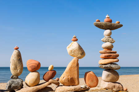 Several Rock zen pyramids of colorful pebbles on a beach on the background of the sea. Concept of balance, harmony and meditation