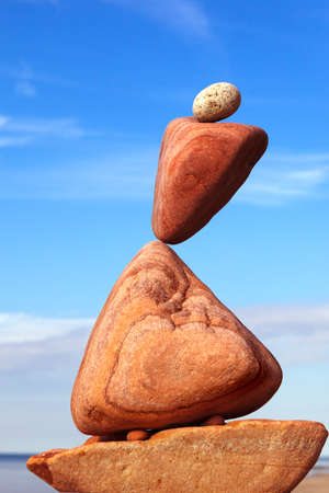 The fall of the pyramid of balanced stones on blue sky background. The concept of fall risk and unstable equilibrium Standard-Bild