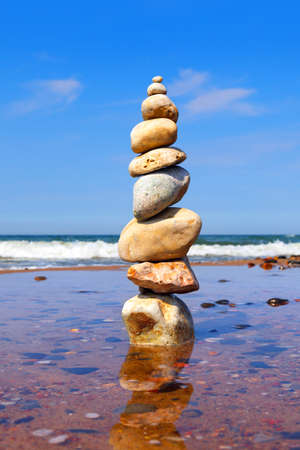 Rock zen pyramid of colorful pebbles standing in the water on the background of the sea. Concept of balance, harmony and meditation Standard-Bild