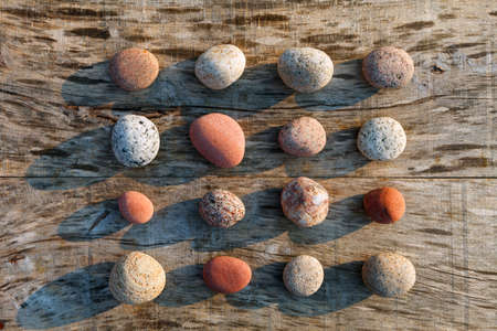 Pattern of multicolored pebbles on a gray old wooden surface. Spa decoration. Meditation and relaxation concept. Flat lay, top view