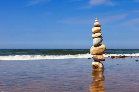 Rock zen pyramid of colorful pebbles standing in the water on the background of the sea. Concept of balance, harmony and meditation 写真素材