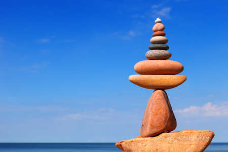 A bright Rock zen pyramid of pink pebbles against a blue sky. Concept of Life balance, harmony and meditation 写真素材