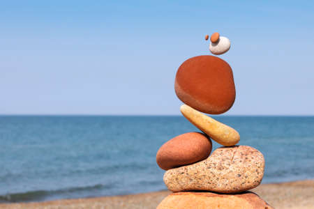 The fall of the pyramid of balanced stones on blue sky background. The concept of fall risk and unstable equilibrium Stockfoto