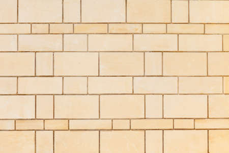 Wall made of smooth, rectangular yellow Sandstone blocks. Background image, texture