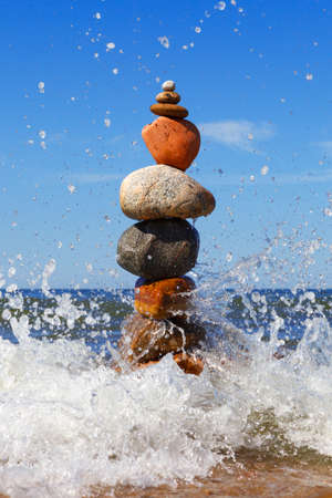 Rock zen pyramid of colorful pebbles standing in the water on the background of the sea and waves. Concept of balance, harmony and meditation Zdjęcie Seryjne