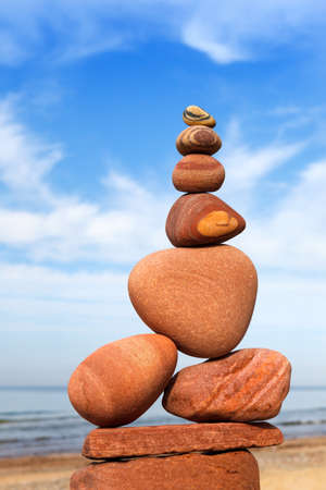 Rock zen pyramid of red and pink pebbles on the beach. Concept of Life balance, harmony and meditation Zdjęcie Seryjne