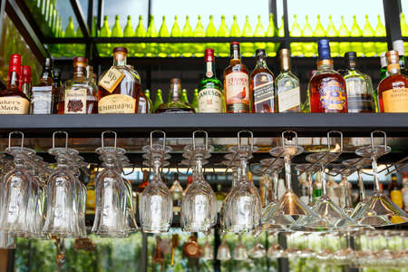 Singapore, Singapore-November 28, 2019: Wine glasses hang over the bar counter on the background of bottles with alcoholic drinks. Soft focus, selective focus