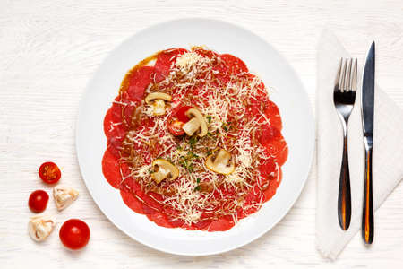 beef carpaccio is beautifully served on a white plate and garnished with tomatoes, champignons and cheese. Top view