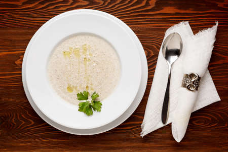 Mushroom soup in a white plate on a dark wooden table with a napkin and spoon. Top view