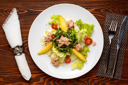 Classic Nicoise Salad On a white plate, on a dark wooden table with a knife, fork and napkin. Top view 写真素材 - 158632215