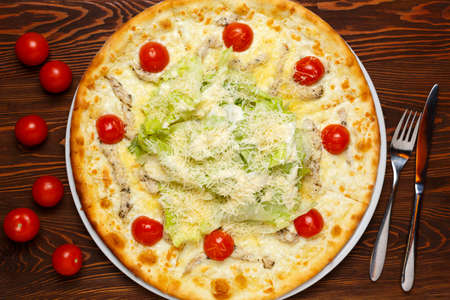 Pizza with chicken, cheese, herbs and tomatoes