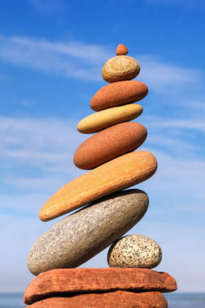 Rock zen pyramid of red and yellow pebbles on the beach. Concept of Life balance, harmony and meditation Stockfoto