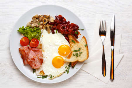 English Breakfast, fried eggs, ham, mushrooms on a white plate with a knife and fork, on a white wooden table. top view 写真素材