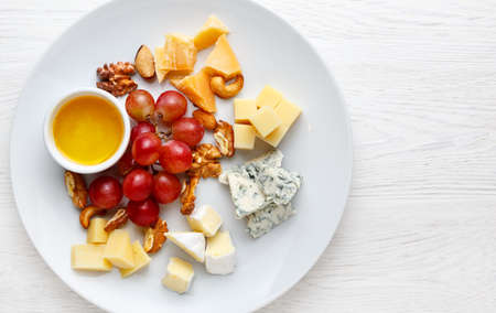 Cheese plate served with grapes and nuts. Assorted cheeses Camembert, Brie, Parmesan blue cheese, goat. Top view 写真素材