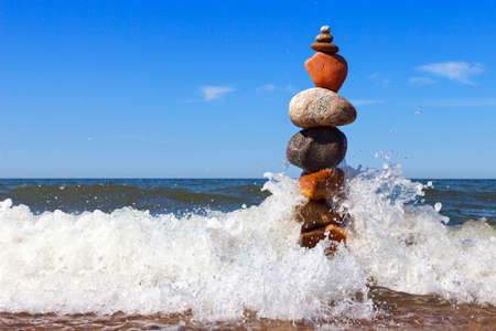 Rock zen pyramid of colorful pebbles standing in the water on the background of the sea and waves. Concept of balance, harmony and meditation 写真素材