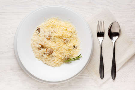 Mushroom risotto on a white plate on a white wooden table. Top view 写真素材 - 158701430