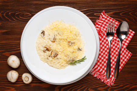 Mushroom risotto on a white plate on a dark wooden table. Top view 写真素材 - 159219741