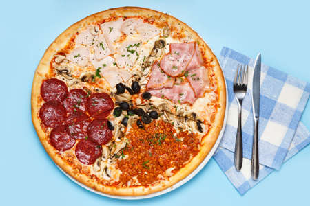 Whole pizza with four different type of toppings on a blue background with a napkin, knife and fork. top view 写真素材 - 159219685