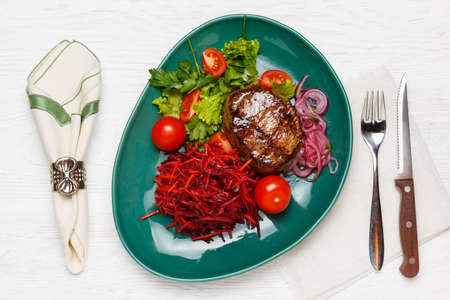 Beef steak with a side dish of carrots, beets and tomatoes on a green plate, on a white wooden table with a napkin, knife and fork. Top view 写真素材 - 160251703