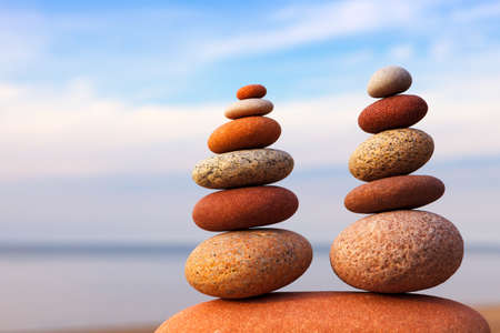 Two Rock zen pyramids of colorful pebbles on a beach on the background of the sea. Concept of Life balance, harmony and meditation