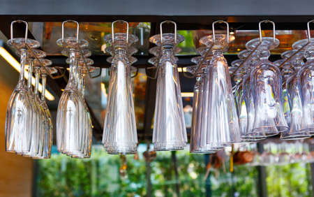 Many wine glasses hang over the bar. Soft focus, selective focus