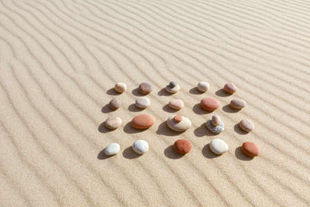 Pattern of colored pebbles on clean sand. The concept of peace
