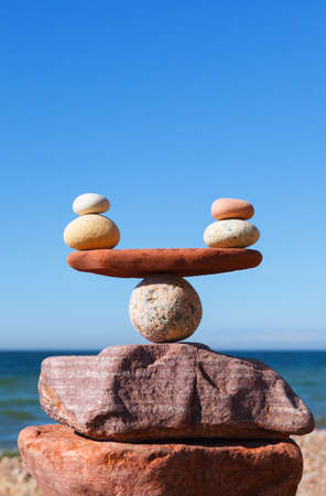 Symbolic scales of stones against the background of the sea and blue sky. Concept of harmony and balance. Pros and cons concept Archivio Fotografico