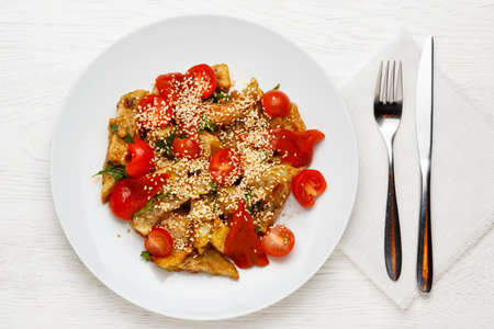 Warm eggplant salad garnished with sesame seeds and sherry tomatoes on a white plate on a white wooden table, fork and spoon. Top view 写真素材