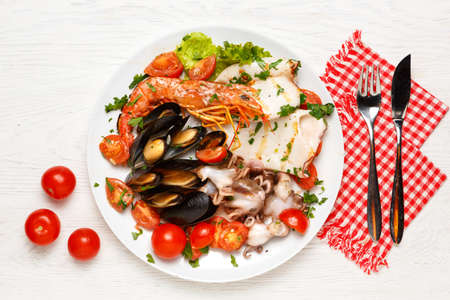 Assorted seafood on a plate on a white wooden table. Napkin, fork and knife for fish, Top view