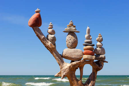 stack of multicolored balanced stones on an old wooden snags, on a blue sky and sea background. Concept of harmony and balance. 写真素材