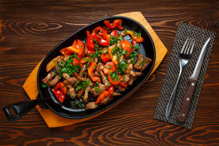 Roast pork with red bell pepper in a frying pan on a dark wooden table, knife, fork, top view 写真素材