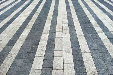 White and black paving slabs made of natural stone lined with stripes. Top view 写真素材