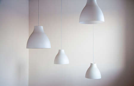 attached: Four white lampshades attached to a ceiling Stock Photo