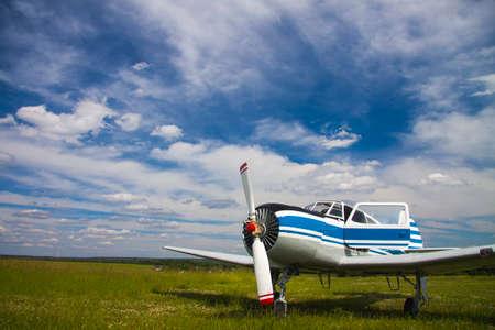 aerodrome: Propeller plane on the aerodrome on cloudy sky background Stock Photo